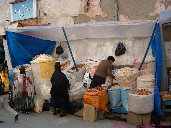 Traditional Bolivian ladies with their Bowler hats and giant bags of pork rinds at the market in La Paz, Bolivia