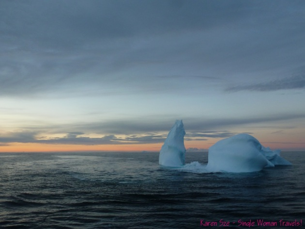 Antarctica iceberg floating in open waters at dusk