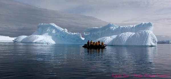 Fellow Antarctic tourists on a zodiac getting a closer look of a small iceberg