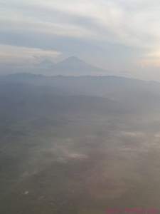 Hazy morning view of Mount Kelud from airplane window