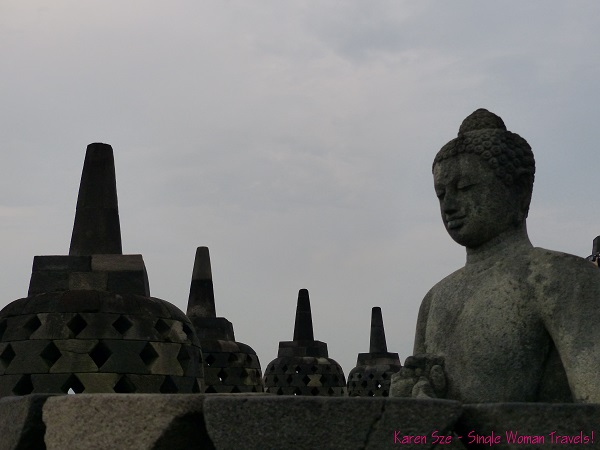 Unveiled Buddha amongst stupas at Borobudur, Indonesia