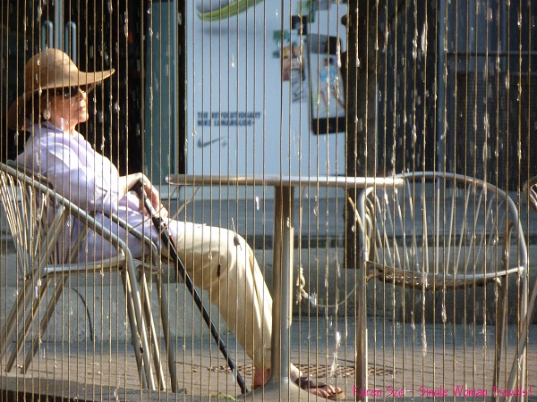 Woman sitting alone in a patio chair with her cane behind a metal water feature