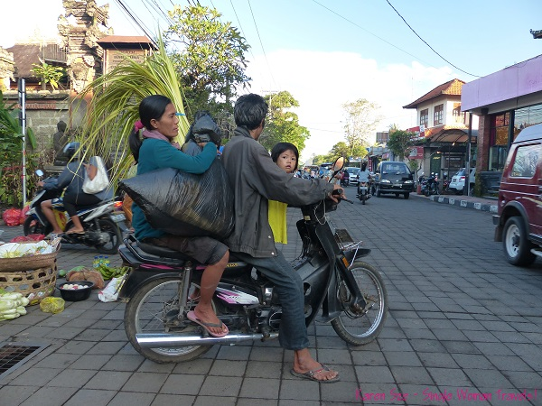 Balinese family of 3 heads home with shopping in Ubud market, Bali, Indonesia