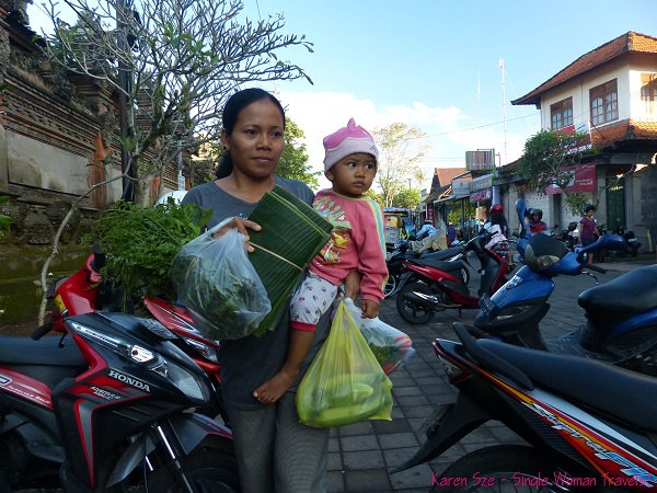 Mother with child takes daily shopping home from Ubud Market