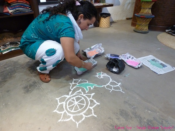 Nepali woman decorates her floor with rangoli for Diwali