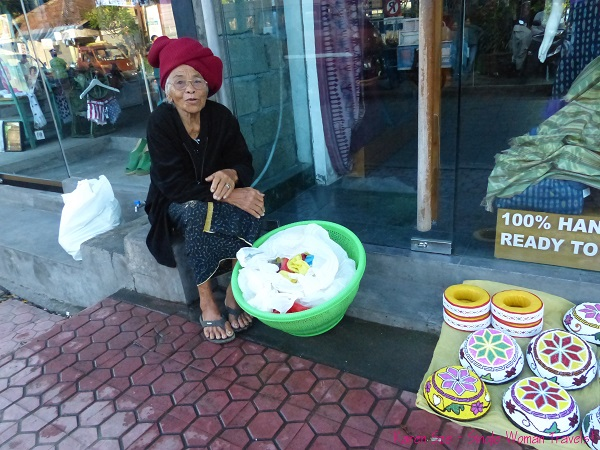 Old Balinese woman selling homemade beaded containers