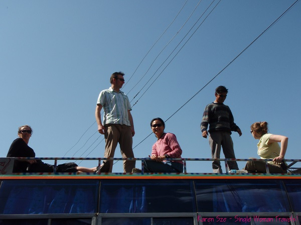 Single Woman and fellow travelers take a seat on top of the bus in Nepal