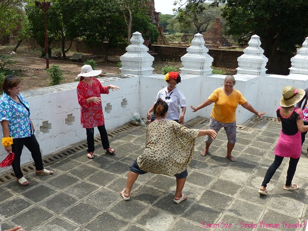 Thai women dancing outside a temple