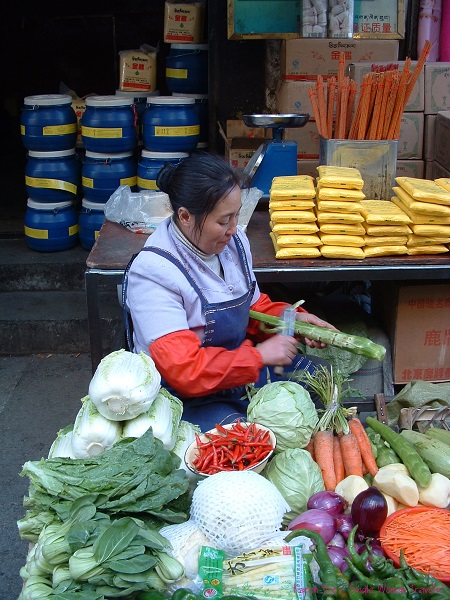 Chinese migrants selling fresh vegetables in market