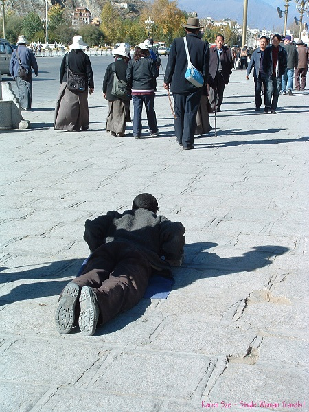 Devoted Tibetan Buddhist in prostration on the Barkhor Kora (Pilgrim circuit) in Lhasa, Tibet