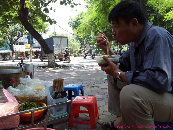 Local Vietnamese eating pho on the street of Hanoi