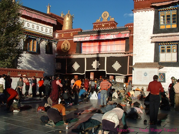 Many Tibetan Buddhists in prayer and prostration in front of Jokhang Temple, Lhasa, Tibet