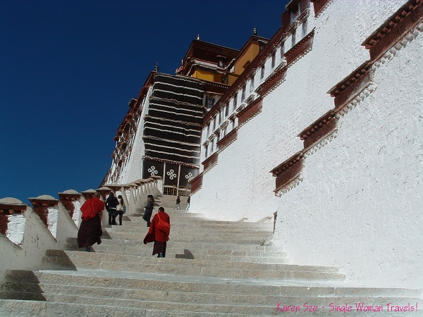 Tibetan monks walking up the stairs to Potala Palace in Lhasa, Tibet