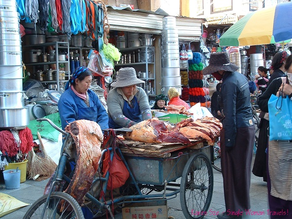 Yak meat sold from back of bicycle by 2 women in Lhasa