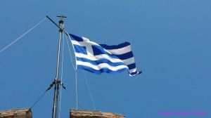 Greek flag flying high above the White Tower of Thessaloniki, Greece