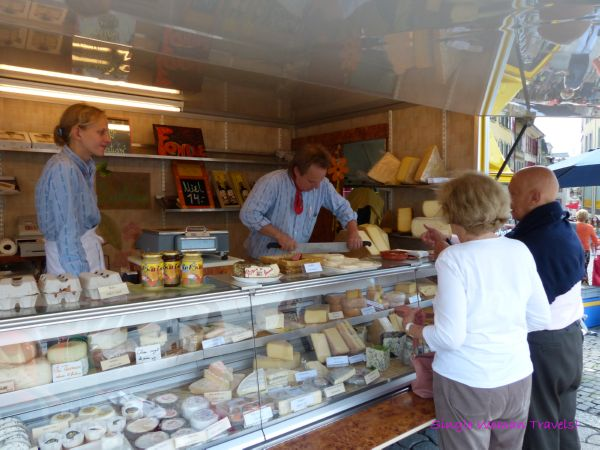 Locals buying cheese from vendor at Lausanne market