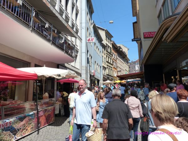 Shoppers arriving and leaving farmer market in Lausanne Switzerland