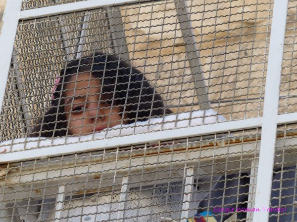 Young girl behind protective fencing on balcony in Hebron Palestine
