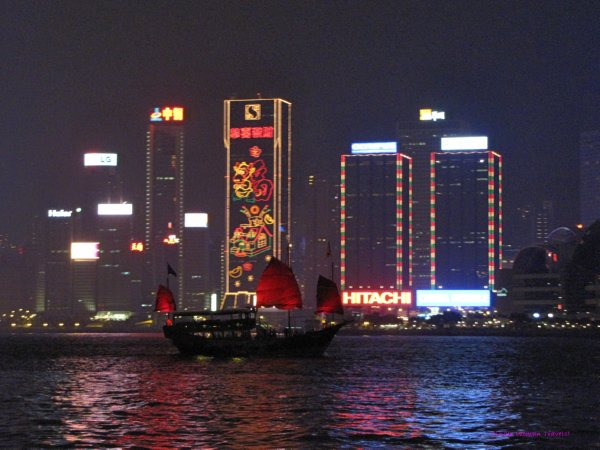 Junk boat in Hong Kong harbour in front of decorated high rise buildings