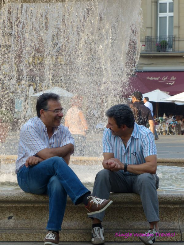 2 man sitting in front of a water fountain in Frankfurt Germany