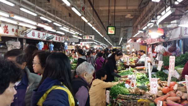Fruit and vegetable vendors and shoppers inside Government built market buildings in Hong Kong